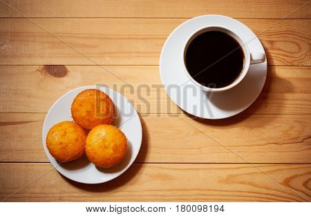 Cakes and cup of coffee on wooden table