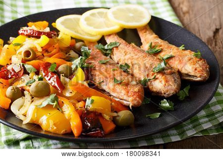 Roasted Red Mullet With Stewed Vegetables, Lemon And Greens Close-up. Horizontal
