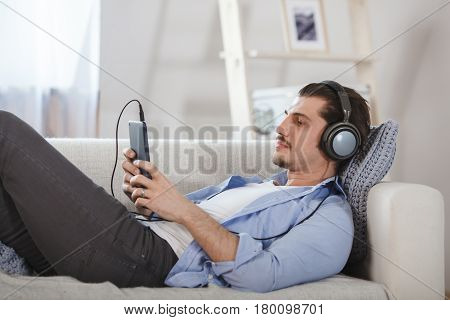 Handsome bearded guy lying on sofa with tablet and headphones