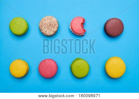 Bite macaroon lying among others on a blue flat lay. Multicolored macaroons over turquoise flatlay
