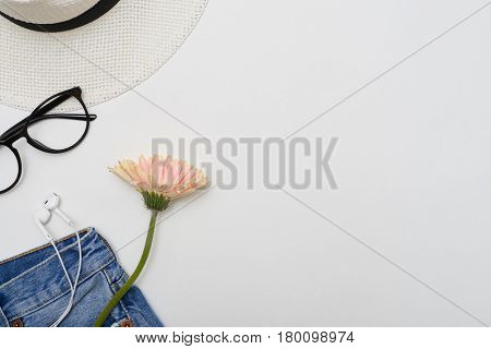 Top view of a cellphone with headphones in the pocket of ripped denim shorts. Summer vacation items. Modern feminine clothes. Well-arranged collection of clothes items with glasses
