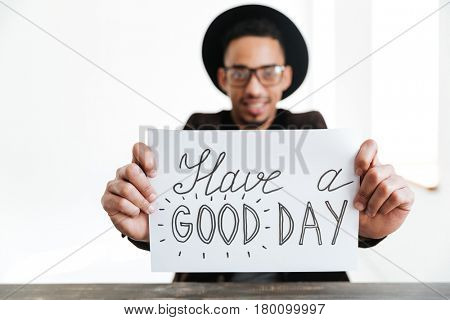 African man in eyeglasses and hat showing sheet of paper at camera. Focus on paper. Have a good day