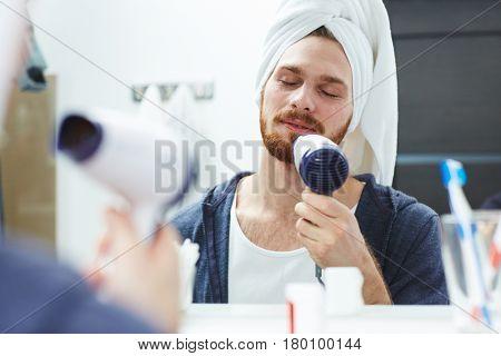 Man with blow-dryer enjoying warm air