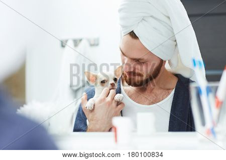 Reflection of young man with his pet in mirror of bathroom