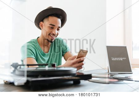 Young African man in t-shirt and hat sitting by the table with record-player and records while using smartphone