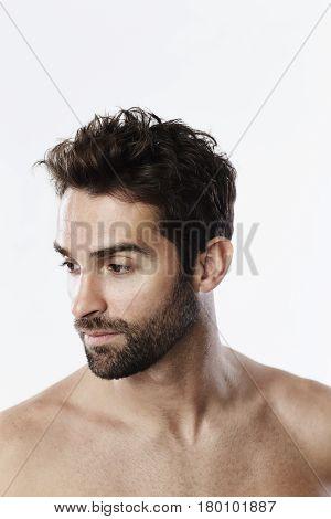 Handsome shirt less guy looking away studio shot
