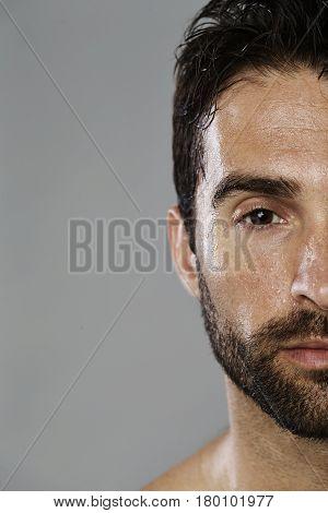 Sweaty guy with stubble portrait studio shot