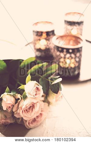 Beautiful bouquet of roses and candles in oriental candlesticks, elegant floral home decorations, vintage filtered