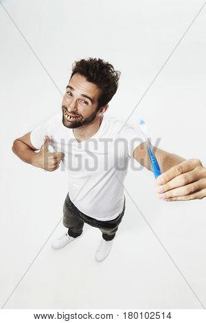 Gap tooth guy holding toothbrush portrait studio shot