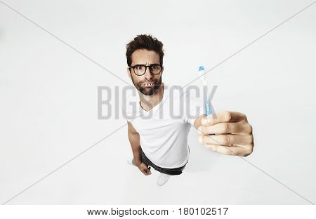 Man with gap teeth holding toothbrush frowning