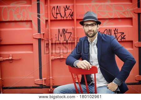 Jacket and hat guy in front of container portrait