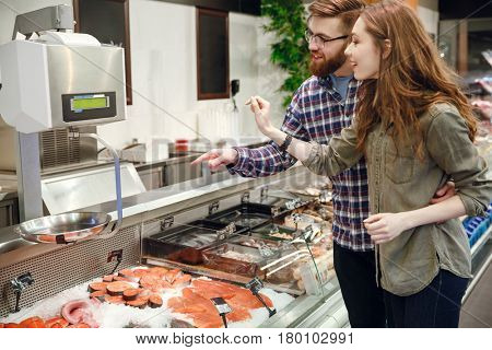 Side view of a pretty couple choosing fish in supermarket