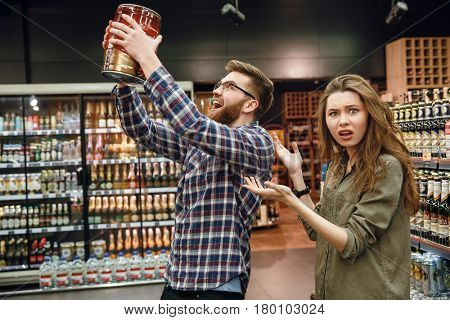Displeased woman showing at the man with keg of beer in hands