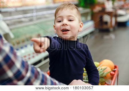 Happy boy sitting on shopping trolley in supermarket and pointing away while his father pushing the trolley