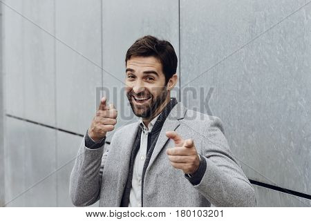 Handsome Smiling guy pointing fingers portrait succes