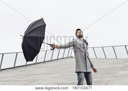 Handsome Guy holding umbrella on windy day