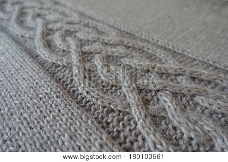 Close-up of grey handmade knit fabric with plait pattern