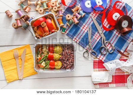 Desktop with lunch box healthy food delivery for dressmaker. Flat lay shot of foil container with diet meal for fashion designer at workplace. Healthy nutrition, brown rice, vegetables