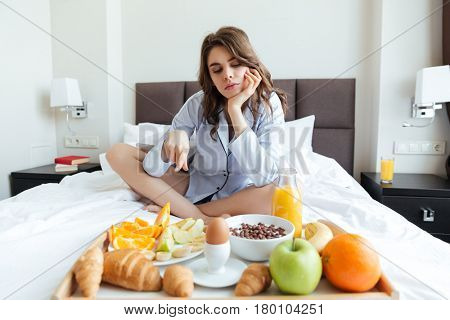 Portrait of a young attractive woman sitting on bed and pointing finger at tray with continental breakfast