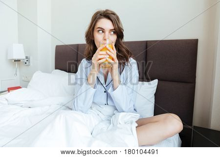Portrait of a young pretty woman wearing nightwear and drinking orange juice while sitting on bed at home in the morning