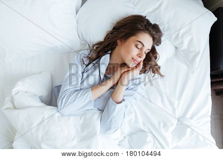 Top view of young beautiful woman in pajamas sleeping peacefully in bed at home