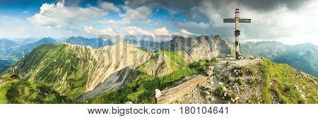 Wooden summit cross and summer colors. Morning or evening light in the mountains. Hiking in the mountains and taking a rest on a peak. Panoramic view from Rotspitze summi cross towards Nebelhorn and Grosser Daumen. Alps, Bavaria, Allgau, Germany