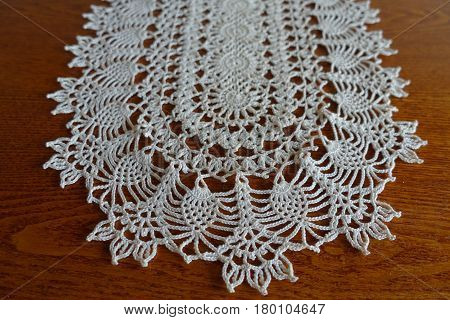 Close-up of oval white crochet lace hanmdmade doily on wood