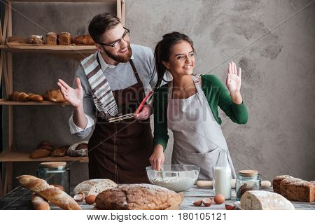Happy couple looking away wile cooking bread and greeting with someone