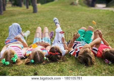 Group of children in colorful summer wear lying on their backs on green lawn in park and eating lollipops