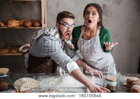 Shocked man and suprised woman trying to catch something on table with products