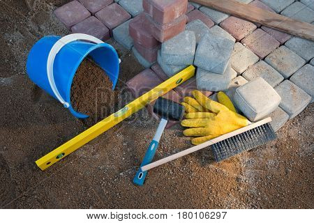 Pavement details stone blocks rubber hammer level gloves and tape measure