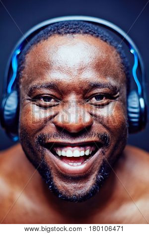 Studio shot of joyful middle-aged man listening to music in headphones and looking at camera with wide smile