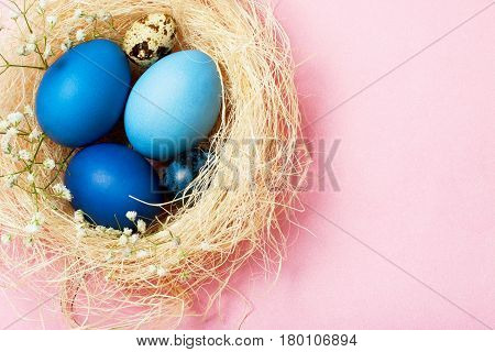 Easter eggs in blue colors in a nest on the pink background. The place for the text. The concept of stylish decoration for Easter greeting cards etc. Flat lay