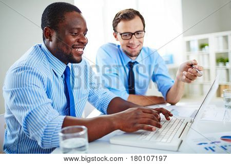 Bearded worker in eyeglasses looking at camera with wide smile while his African American colleague writing email to business partner