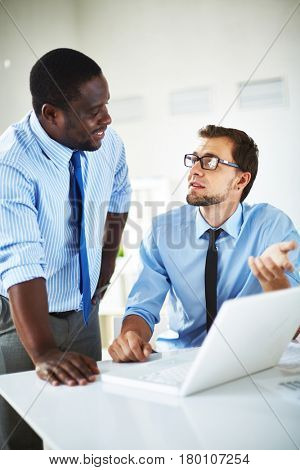 Bearded employee with eyeglasses sitting at office desk and showing results of accomplished work to his middle-aged superior