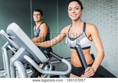 Portrait of beautiful  sportive brunette woman exercising using elliptical machine  next to fit man, both smiling to camera during workout in modern gym