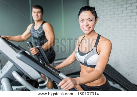 Portrait of beautiful  sportive brunette woman exercising using elliptical machine  next to fit man, both smiling looking at camera during workout in modern gym