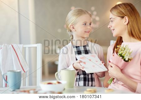 Cute girl showing her mother self-made greeting-card