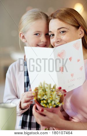 Cheerful woman anad her little daughter peeking out of open greeting-card