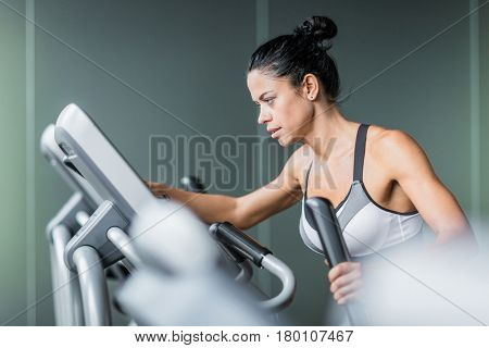 Side view  portrait of beautiful  sportive  woman exercising using elliptical machine   during intense workout in modern gym