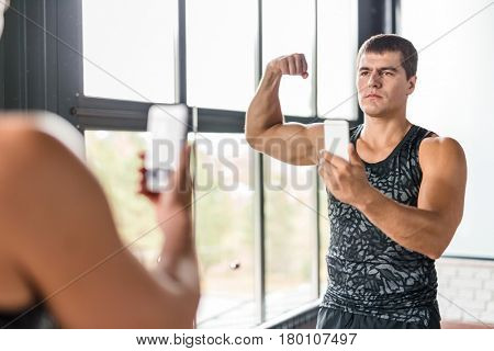 Portrait of proud bodybuilder boasting his arm muscles taking selfie in gym  mirror flexing biceps after working out