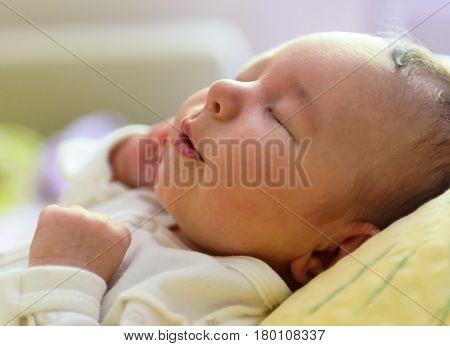 Newborn baby (girl) sleeping peacefully at home