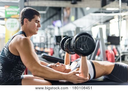 Portrait of muscular personal instructor helping beautiful woman doing weightlifting exercise with big dumbbells on bench  in modern gym