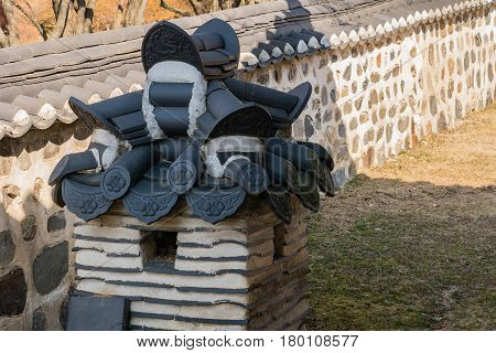 Oriental style kennel with tiled roofing next to a stone wall located in a public park in South Korea