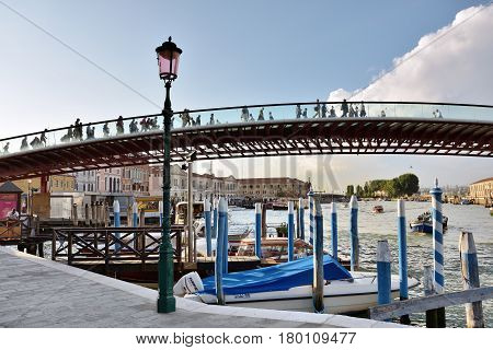 VENICE ITALY - SEPT 22 2014: People hurry at work in the morning pass the bridge of the Constitution in Venice. Most residents work outside the historic city