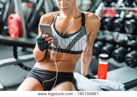 Mid section shot of unrecognizable fit tanned woman wearing sportswear sitting on bench in gym with smartphone, resting after workout