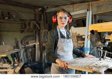 Beautiful drill press operator in eye and ear protectors posing for photography with serious look while distracted from work, waist-up portrait