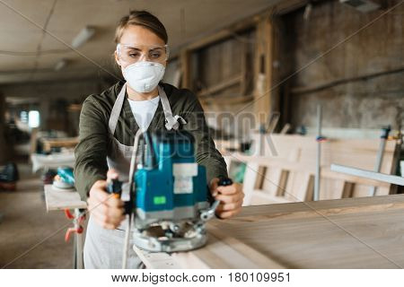 Young carpenter wearing filter mask and eye protectors while practicing at sanding wooden work piece in spacious workshop, waist-up portrait
