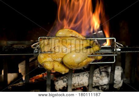 Whole chicken on a spit over a fire
