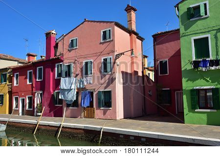 BURANO ITALY - SEPT 23 2014 : Colorful facades of the houses on the famous island Burano. Venice and the Venetian lagoon are on the UNESCO World Heritage List